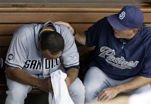 San Diego Padres coach Darren Balsley tries to settle pitcher Edinson Volquez after the third inning of a baseball game against the Dodgers in Los Angeles, Saturday, July 14, 2012. (AP Photo/Reed Saxon)