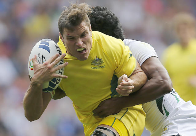 Australia's Ed Jenkins, left, and Sri Lanka's Fazil Marija challenge for the ball during the Rugby Sevens Pool D match 1 between Australia and Sri Lanka at the Ibrox stadium during the Commonwealth Games 2014 in Glasgow, Scotland, Saturday July 26, 2014. (AP Photo/Frank Augstein)