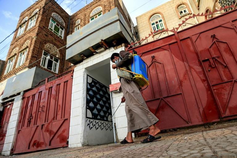 A volunteer in a community-led initiative to prevent the spread of COVID-19 sterilises a street in Yemen's capital Sanaa