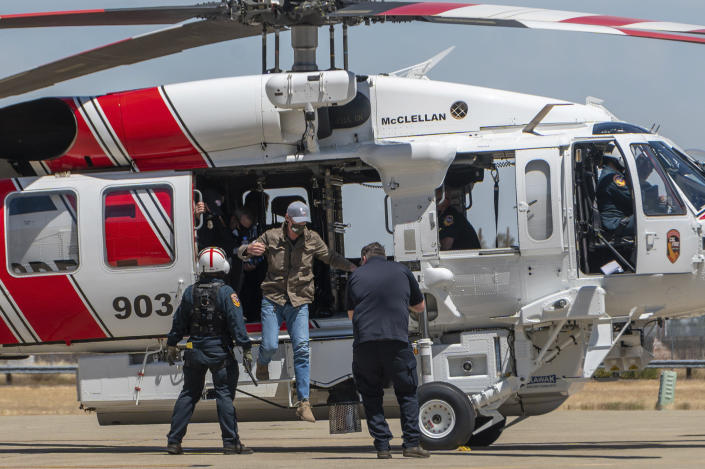 California Gov. Gavin Newsom jumps out of a new Sikorsky S70i Black Hawk firefighting helicopter after arriving to highlight new firefighting equipment and his proposed $2 billion investment in wildfire and emergency preparedness at a press conference in McClellan Park in Sacramento County on Monday, May 24, 2021. (Renee C. Byer/The Sacramento Bee via AP)