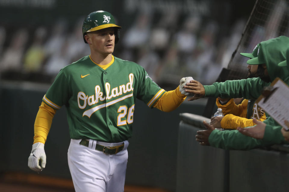Oakland Athletics' Matt Chapman is congratulated by teammates after scoring on a single by Sean Murphy against the Detroit Tigers during the fourth inning of a baseball game in Oakland, Calif., Friday, April 16, 2021. (AP Photo/Jed Jacobsohn)