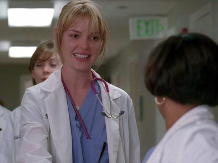 Katherine Heigl as Izzie on Greys Anatomy, shaking Baileys hand and wearing scrubs and a coat