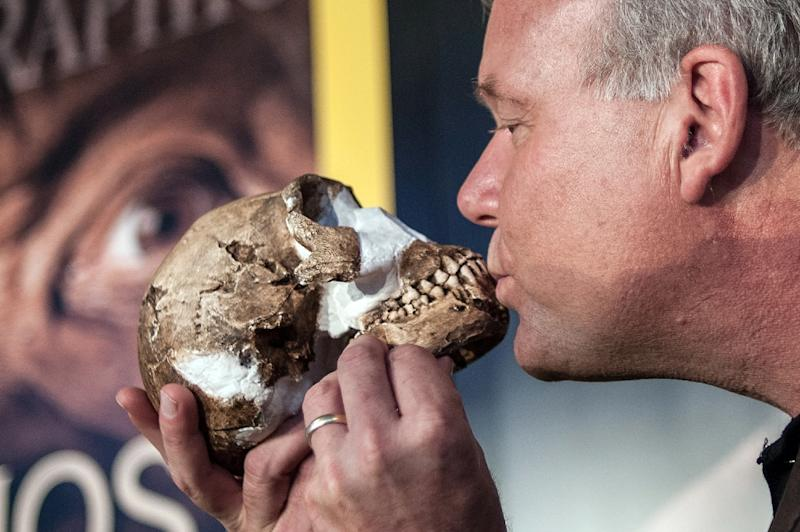 Professor Lee Berger kisses a replica of the skull of a Homo Naledi -- a newly discovered human species -- during the unveiling ceremony in Maropeng, on September 10, 2015 (AFP Photo/Stefan Heunis)