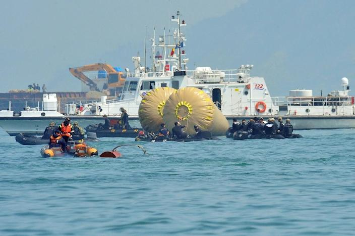 Rescue team personnel take part in recovery operations at the site of the sunken Sewol ferry, marked with buoys, at sea off Jindo off the southeast coast of South Korea on April 24, 2014 (AFP Photo/Jung Yeon-Je)