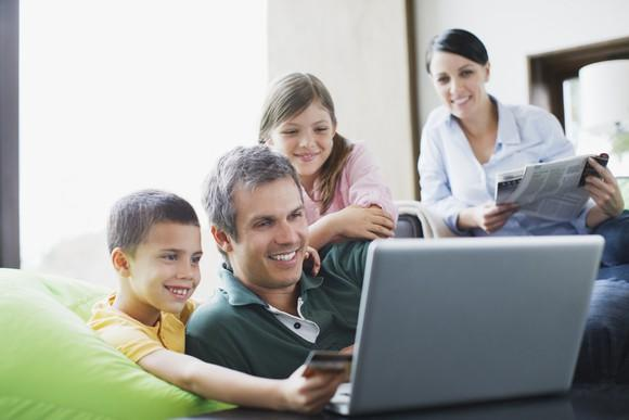 The family huddles around a laptop looking at the screen, smiling, while a child holds a credit card