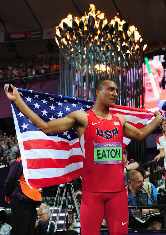 LONDON, ENGLAND - AUGUST 09:  Ashton Eaton of the United States celebrates under the Olympic Cauldron after winning gold in the Men's Decathlon on Day 13 of the London 2012 Olympic Games at Olympic Stadium on August 9, 2012 in London, England.  (Photo by Stu Forster/Getty Images)