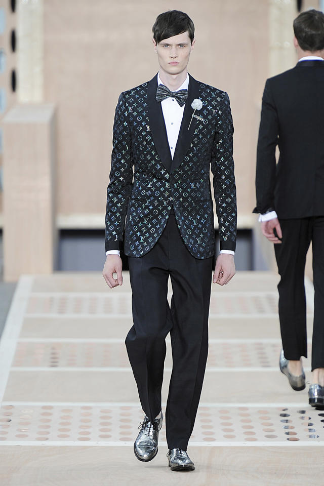 <p>At Louis Vuitton, black-tie suiting is never simple. Here, a model wears an iridescent Louis Vuitton monogrammed blazer with metallic silver oxfords and shimmery bow tie. (Photo: Catwalking) </p>