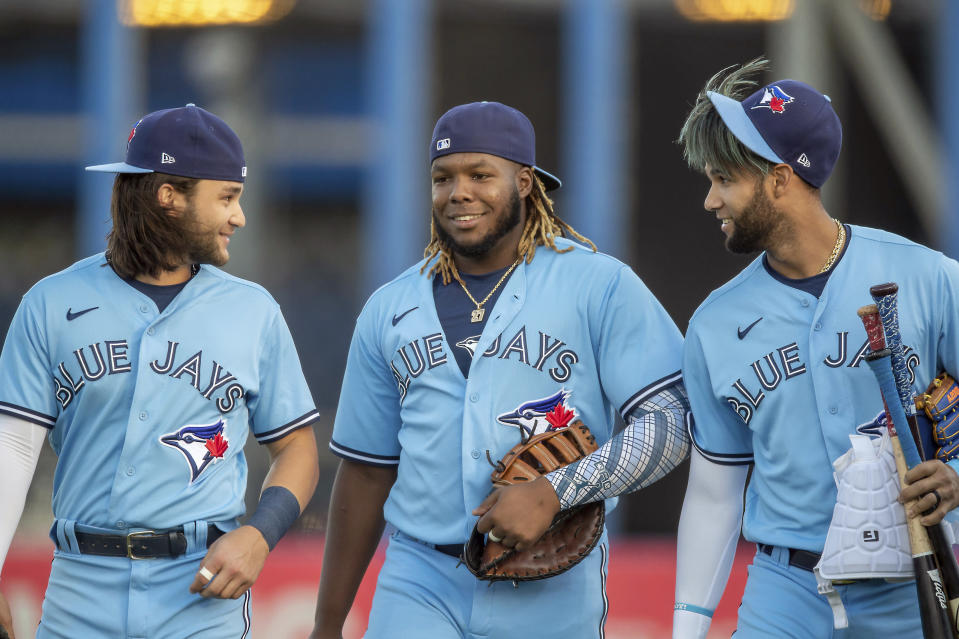 Toronto Blue Jays' Bo Bichette, Vladimir Guerrero Jr. and Lourdes Gurriel Jr., from left, walk onto the field for the team's baseball game against the Boston Red Sox on Tuesday, May 18, 2021, in Dunedin, Fla. (AP Photo/Mike Carlson)