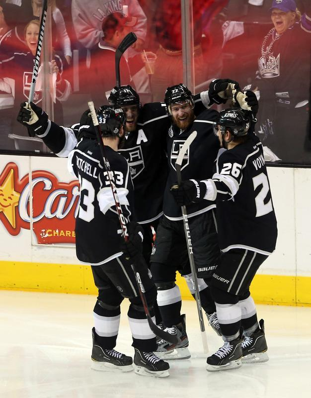 LOS ANGELES, CA - JUNE 11: Willie Mitchell #33, Anze Kopitar #11 and Slava Voynov #26 of the Los Angeles Kings celebrate with teammate Jeff Carter #77 of the Los Angeles Kings after Carter scored in the second period of Game Six of the 2012 Stanley Cup Final against the New Jersey Devils at Staples Center on June 11, 2012 in Los Angeles, California. (Photo by Bruce Bennett/Getty Images)