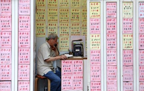 An property agent talks on the phone inside a real estate agency in Wan Chai. Photo: Felix Wong