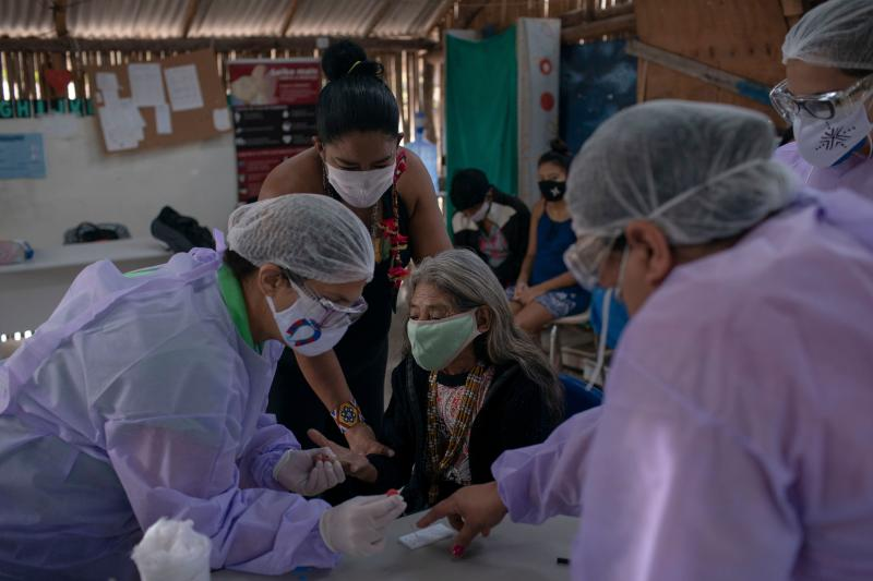Health professionals administer a COVID-19 test to a Guarani indigenous woman at a Health Care indigenous post at the Sao Mata Verde Bonita tribe camp, in Guarani indigenous land, in Marica, Rio de Janeiro state, Brazil, on July 2, 2020, amid the new coronavirus pandemic. - Despite the proximity of urban regions heavily infected with COVID-19, the indigenous territory is managing to keep the deadly virus away from its residents. (Photo by MAURO PIMENTEL / AFP) (Photo by MAURO PIMENTEL/AFP via Getty Images)