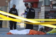 <p>Police officers stand near one of the bodies on the street after a van drove up on the curb and hit several pedestrians in Toronto. LARS HAGBERG/AFP/Getty Images </p>
