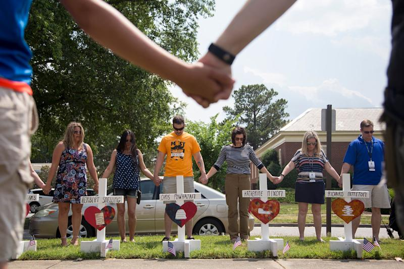 Community members hold hands and pray around the 12 crosses at the memorial located by Building 11 of the Municipal Center, June 2, 2019, in Virginia Beach, Va. (Photo: Sarah Holm/The Virginian-Pilot via AP)
