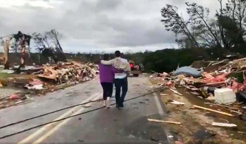 People walk amid debris in Lee County, Ala., after what appeared to be a tornado struck in the area, March 3, 2019. Severe storms destroyed mobile homes, snapped trees and left a trail of destruction amid weather warnings extending into Georgia, Florida and South Carolina, authorities said. (Photo: WKRG-TV via AP)