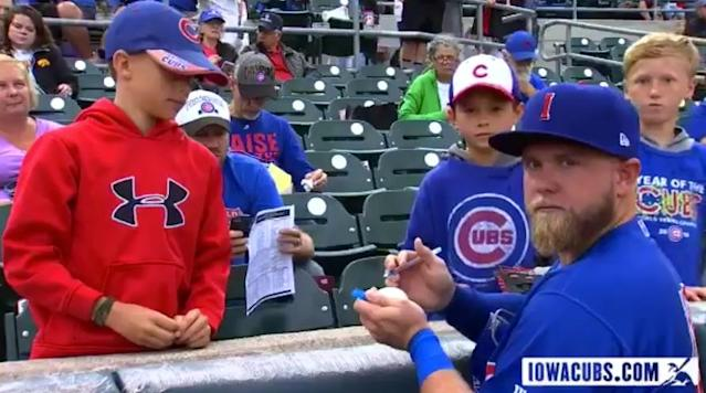 Taylor Davis might be signing a ball for a young fan, but he knows the camera is there. (Twitter/@IowaCubs)