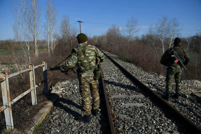 Greek soldiers stand on the railway tracks as they patrol next to the Greek-Turkish border near the village of Marasia, in the region of Evros