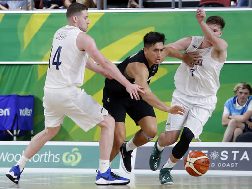Reuben Te Rangi of New Zealand drives through the defense of Christopher Cleary, left, and Malcolm Fraser of Scotland during their bronze medal men's basketball game at the Gold Coast Convention and Exhibition Centre during the 2018 Commonwealth Games on the Gold Coast, Australia, Sunday, April 15, 2018. (AP Photo/Mark Schiefelbein)