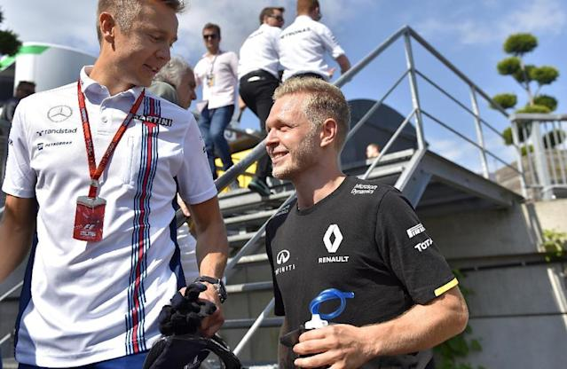 Renault Sport F1 Team's Danish driver Kevin Magnussen (R) walks in the paddocks at the Spa-Francorchamps circuit in Spa on August 28, 2016 ahead of the Belgian Formula One Grand Prix. (AFP Photo/LOIC VENANCE)