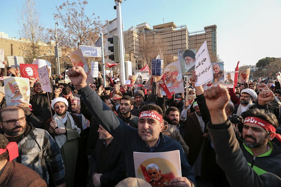 """Iranian demonstrators hold placards bearing the images of slain military commander Qasem Soleimani and Iran's Supreme Leader Ayatollah Ali Khamenei in front of the British embassy in the capital Tehran on January 12, 2020 following the British ambassador's arrest for allegedly attending an illegal demonstration. - Chanting """"Death to Britain"""", up to 200 protesters rallied outside the mission a day after the brief arrest of British ambassador Rob Macaire at a memorial for those killed when a Ukraine airliner was shot down. (Photo by ATTA KENARE / AFP) (Photo by ATTA KENARE/AFP via Getty Images)"""
