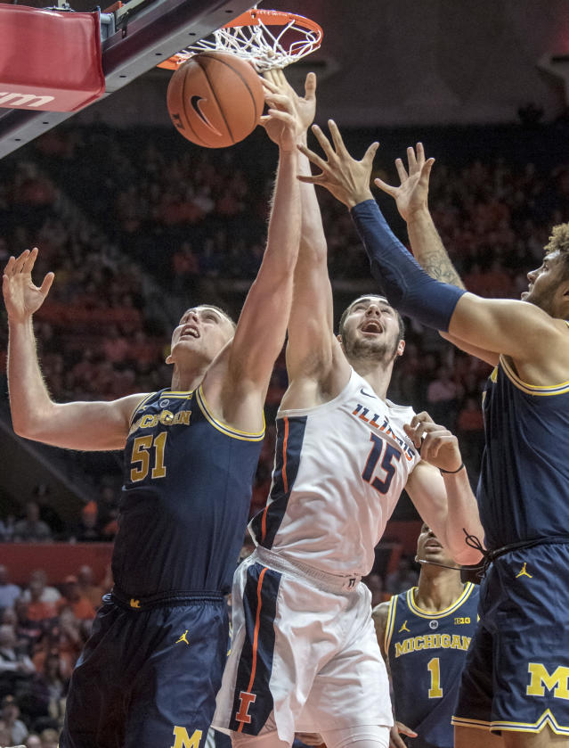 Michigan forward Austin Davis (51) and Michigan forward Isaiah Livers (4) go up for a rebound with Illinois forward Giorgi Bezhanishvili during the first half of an NCAA college basketball game in Champaign, Ill., Thursday, Jan. 10, 2019. (AP Photo/Rick Danzl)