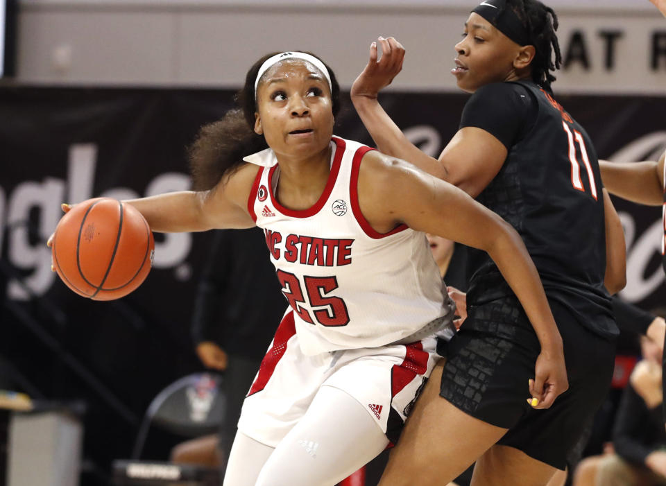 North Carolina State's Kayla Jones (25) drives around Virginia Tech's D'asia Gregg (11) during the first half of an NCAA college basketball game, Sunday, Jan. 24, 2021 in Raleigh, N.C. (Ethan Hyman/The News & Observer via AP)