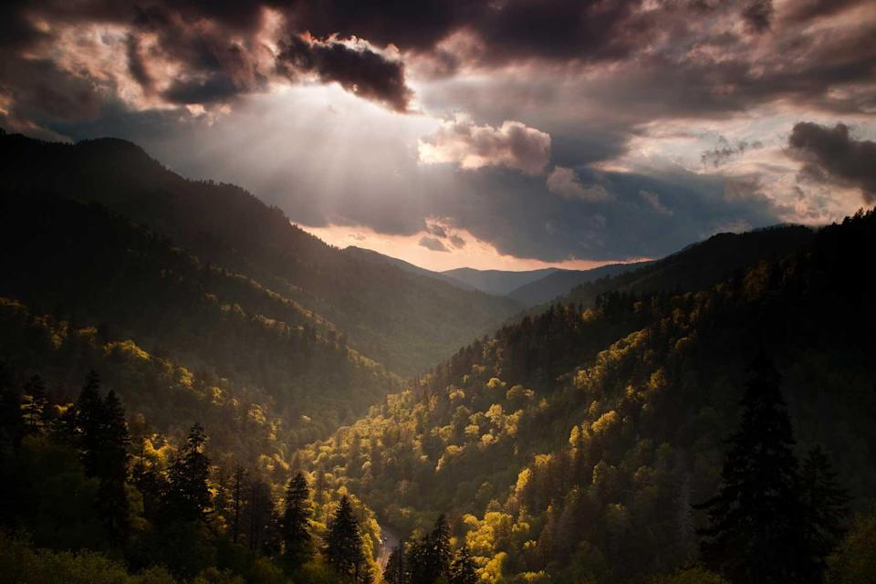 Clearing storm clouds and a descending sun at dusk combine to provide dramatic lighting and highlighted mountainsides as viewed from the Morton Overlook at the Great Smoky Mountain National Park.