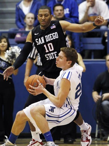 Air Force guard Max Yon, front, picks up a loose ball as San Diego State forward Tim Shelton looks on in the second half of Air Force's 58-56 victory in an NCAA basketball game at Air Force Academy, Colo., on Saturday, Feb. 18, 2012. (AP Photo/David Zalubowski)