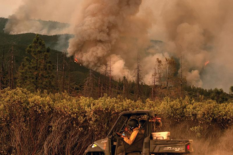 Firefighters drive along a fire break as the Ferguson fire burns in Stanislaus National Forest near Yosemite National Park on July 21. (NOAH BERGER via Getty Images)