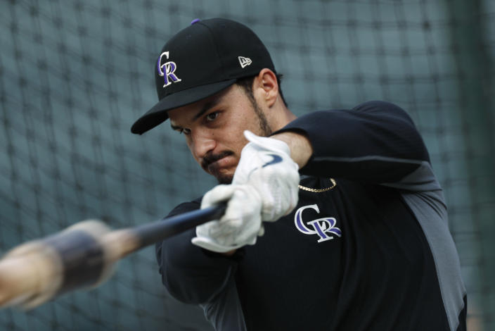 FILE - In this Friday, Sept. 27, 2019, file photo, Colorado Rockies third baseman Nolan Arenado warms up before a baseball game against the Milwaukee Brewers in Denver. Team owner Dick Monfort and general manager Jeff Bridich will hold a zoom press conference Tuesday, Feb. 2, 2021, to discuss the trade of the team's star third baseman, Nolan Arenado, to the St. Louis Cardinals. (AP Photo/David Zalubowski, File)