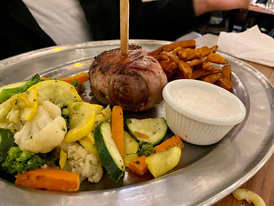 Bacon-wrapped filet mignon with mixed vegetables and sweet potato fries