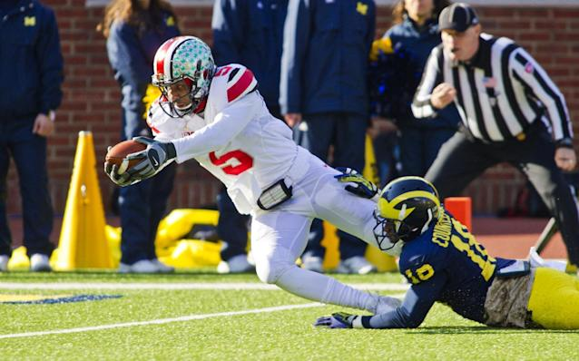 Ohio State quarterback Braxton Miller (5) dives in for a touchdown as Michigan defensive back Blake Countess (18) tries to stop him during the first quarter of an NCAA college football game in Ann Arbor, Mich., Saturday, Nov. 30, 2013. (AP Photo/Tony Ding)