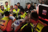 Israeli rescue workers carry a body outside a synagogue in Givat Zeev, outside Jerusalem, Sunday, May 16, 2021. Israeli medics say more than 150 people were injured in a fatal collapse of a bleacher at an uncompleted West Bank synagogue. (AP Photo/Sebastian Scheiner)