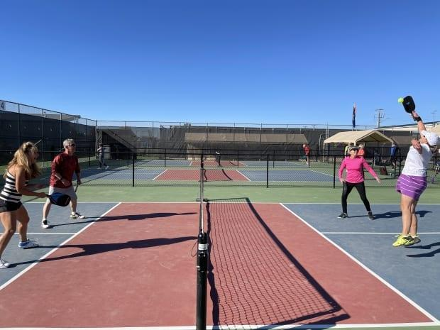 Members of the Parkland Pickleheads squaring off in a doubles match. (Emily Fitzpatrick/CBC - image credit)