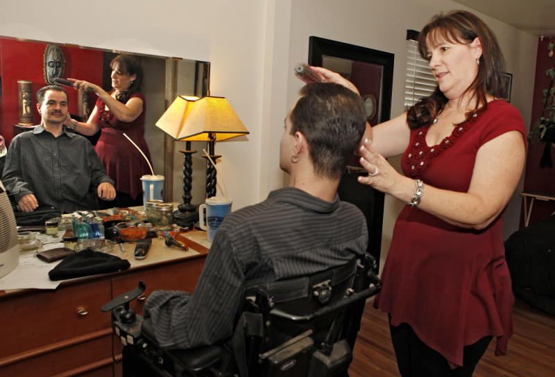 FILE - In this Dec. 6, 2012 file photo, Brandon Coats' mother Donna brushes Brandon's hair at his home in Denver. Coats, a quadriplegic medicalmarijuana patient, was fired from his job in 2010 as a telephone operator at Dish Network after testing positive for marijuana. The Colorado Court of Appeals on Thursday, April 25, 2013, upheld the firing of Coats, saying that there is no employment protection for people who use marijuana. In a split decision issued on Thursday, the court said marijuana use is still barred by the federal government, even though state-licensed marijuana use has been approved by voters and is considered lawful. (AP Photo/Ed Andrieski, File)