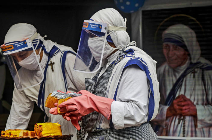 Nuns of the Missionaries of Charity, the order founded by Saint Teresa, wearing masks and face shields as precaution against the coronavirus distribute food to poor and homeless people in Kolkata, India, Wednesday, Aug. 26, 2020. Wednesday marked the birth anniversary of Nobel laureate Mother Teresa, a Catholic nun who spent 45-years serving the poor, the sick, the orphaned, and the dying. (AP Photo/Bikas Das)