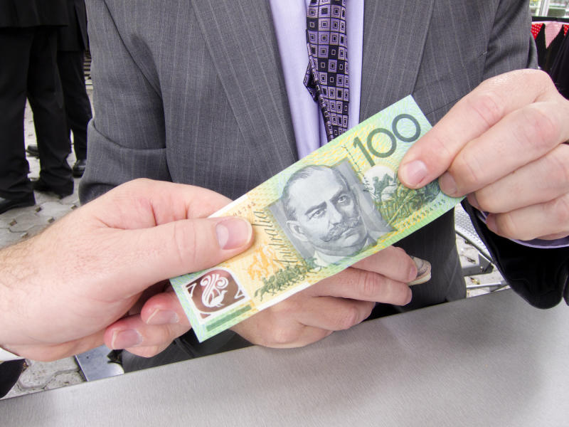 A man in a suit is holding a $100 note. Another man is holding the other side of the note.