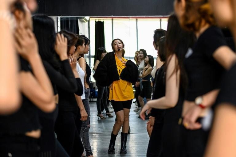 Instructor Pham Kieu Ly (C) demonstrates a pose to participants during a course teaching them how to pose for photographs on their mobile phones at a studio in Hanoi