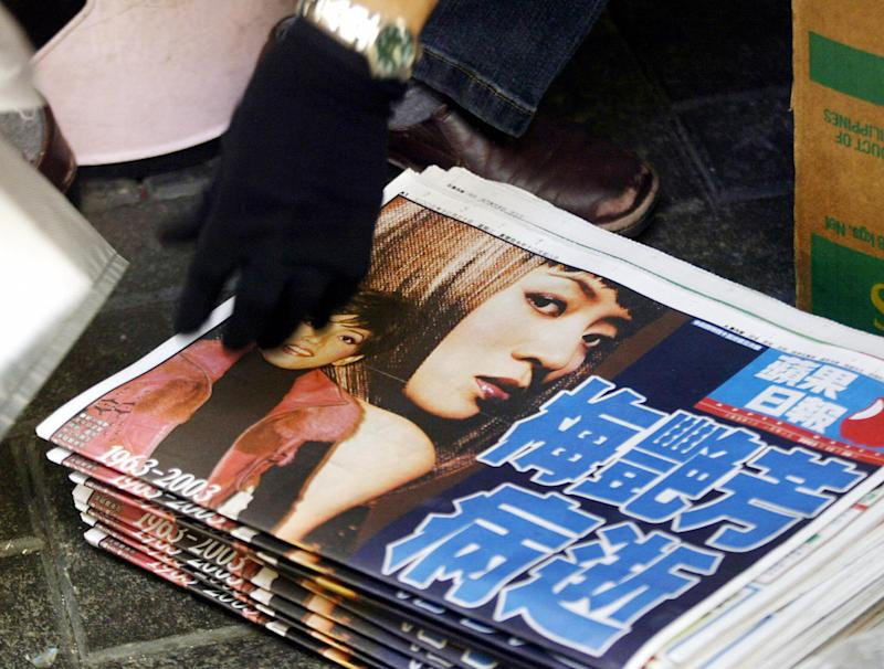 HONG KONG, CHINA: Local newspapers carry pictures of Canto-pop star Anita Mui who died overnight from complications of cervical cancer, 30 December 2003. Friends of the 40-year-old singer including movie star Jackie Chan flocked to her bedside after she was admitted to hospital late Monday and was confirmed dead early Tuesday morning. AFP PHOTO/Peter PARKS (Photo credit should read PETER PARKS/AFP/Getty Images)