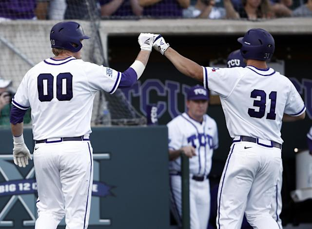 TCU's Kevin Cron (00) is congratulated after scoring on teammate's Jerrick Suiter (31) sacrifice fly against Sam Houston State during the second inning of an NCAA college baseball regional tournament game, Sunday, June 1, 2014, in Fort Worth, Texas. (AP Photo/Jim Cowsert)