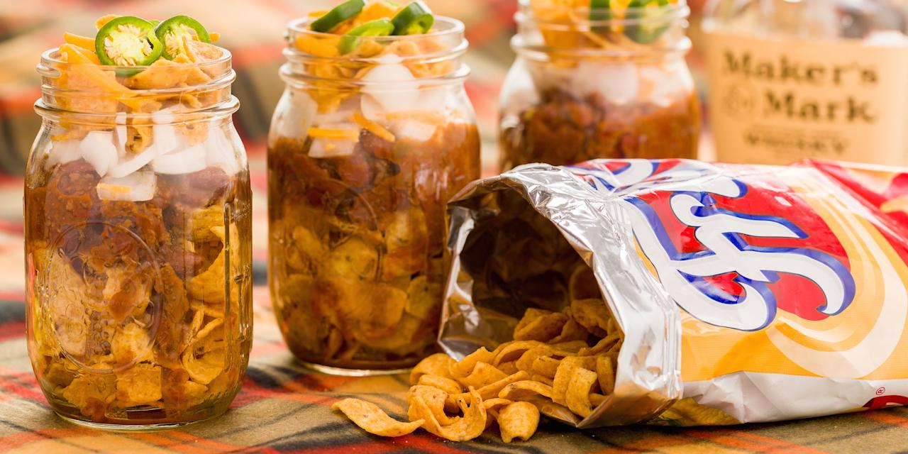 """<p>Tailgating can go one of two ways: solid food spread with subs, burgers, and sides, or sad collection of stale chips and cookies. With these easy in-a-jar meals, you don't have to take the gamble. Frito pie, taco salad, and five-layer dip in a jar = touchdown.  Plus, try our <a rel=""""nofollow"""">amazing tailgate cocktails</a>!</p>"""