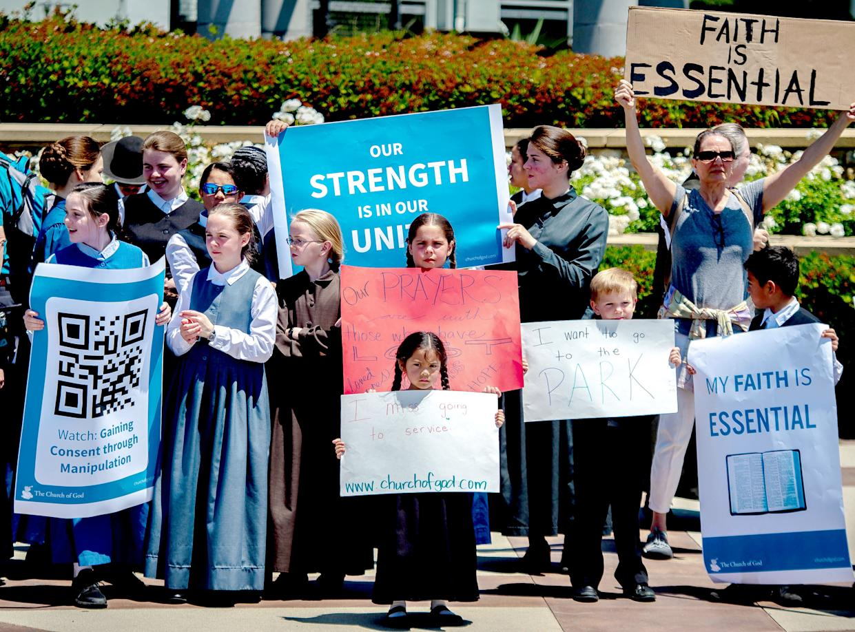 Young members of the Church of God hold signs as they demonstrate against California's stay-at-home orders amid the coronavirus outbreak in Rancho Cucamonga on Sunday, May 3, 2020. (Watchara Phomicinda/MediaNews Group/The Press-Enterprise via Getty Images)