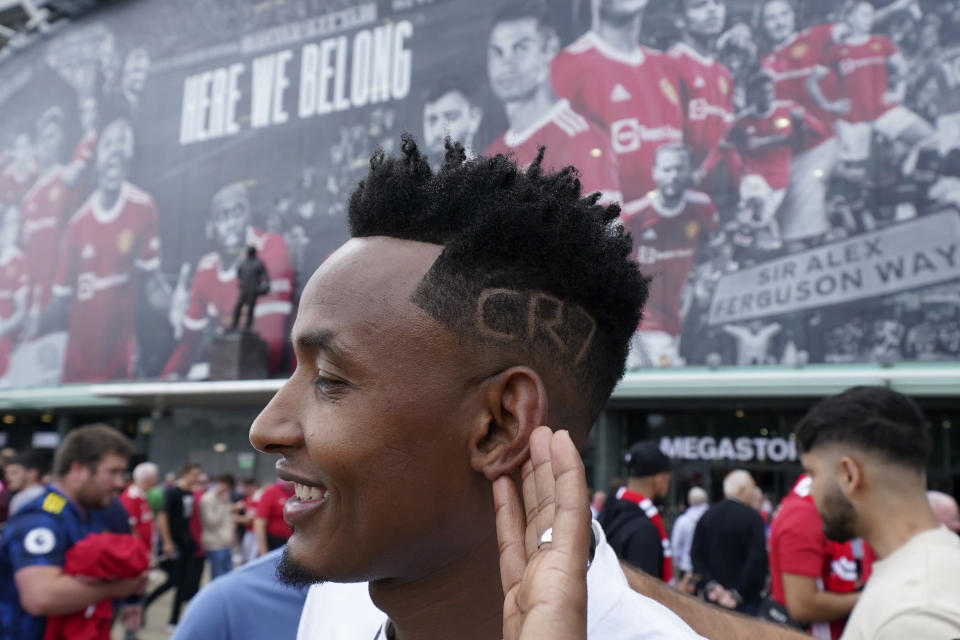 A fan shows off his haircut with a reference to Manchester United's Cristiano Ronaldo outside the stadium before the English Premier League soccer match between Manchester United and Newcastle United at Old Trafford stadium in Manchester, England, Saturday, Sept. 11, 2021. (AP Photo/Jon Super)