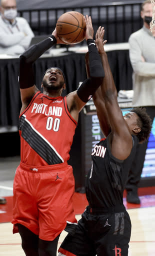 Portland Trail Blazers forward Carmelo Anthony, left, shoots over Houston Rockets forward Jae'Sean Tate during the first half of an NBA basketball game in Portland, Ore., Saturday, Dec. 26, 2020. (AP Photo/Steve Dykes)