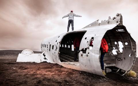 Tourists have their photo taken at the Sólheimasandur plane wreck - Credit: iStock