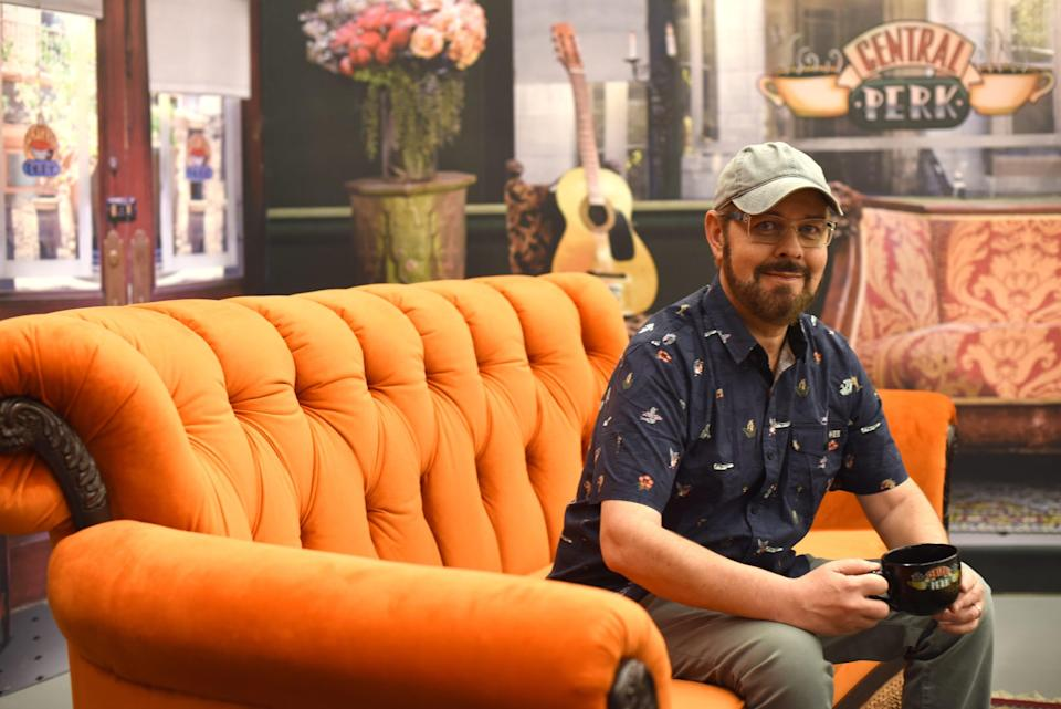 """James Michael Tyler, aka Gunther from """"Friends,"""" sits on an orange couch in the pop-up's Central Perk coffee house."""
