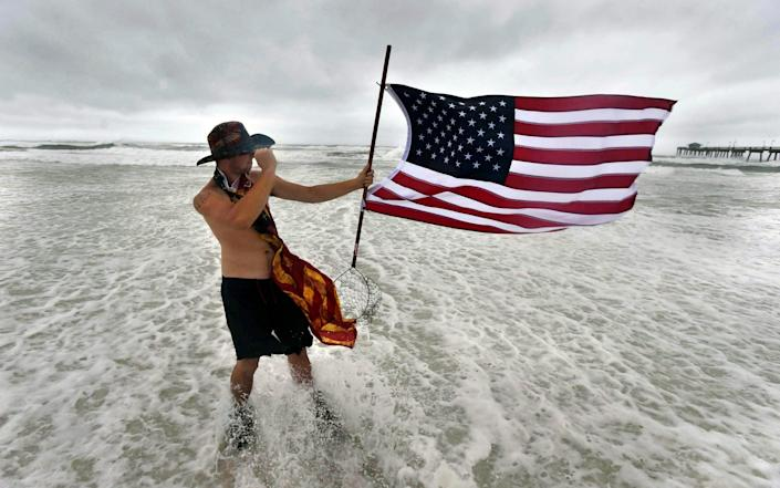 Corbin Boyce holds an American flag on the beach near Fort Walton Beach in Florida - Devon Ravine/Northwest Florida Daily News via AP