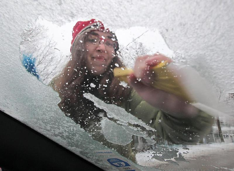 Julia Rhodes works to remove an accumulation of ice from the windshield of her car in Madison, Wis. after freezing rains moved through the area Friday, Dec. 20, 2013. (AP Photo/John Hart, Wisconsin State Journal)