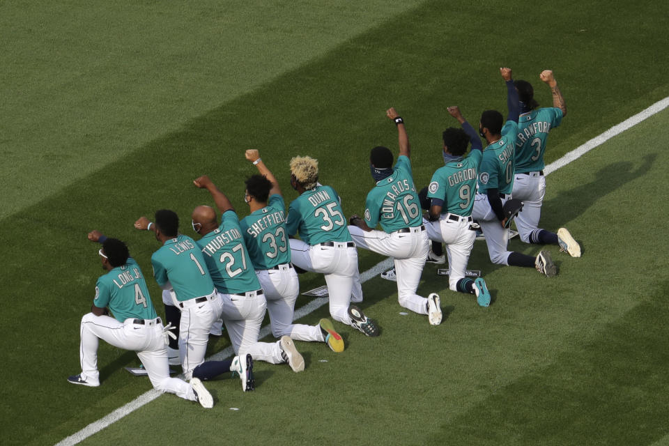 A group of Seattle Mariners players kneel together and raise their fists during a message about the Black Lives Matter movement before the Mariners' home opener baseball game against the Oakland Athletics, Friday, July 31, 2020, in Seattle at T-Mobile Park. (AP Photo/Ted S. Warren)