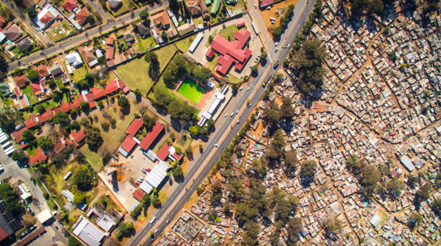<p>Miller's shots of South Africa show large houses sitting next to dwellings made out of scrap and tin (MediaDrumWorld/Johnny Miller) </p>