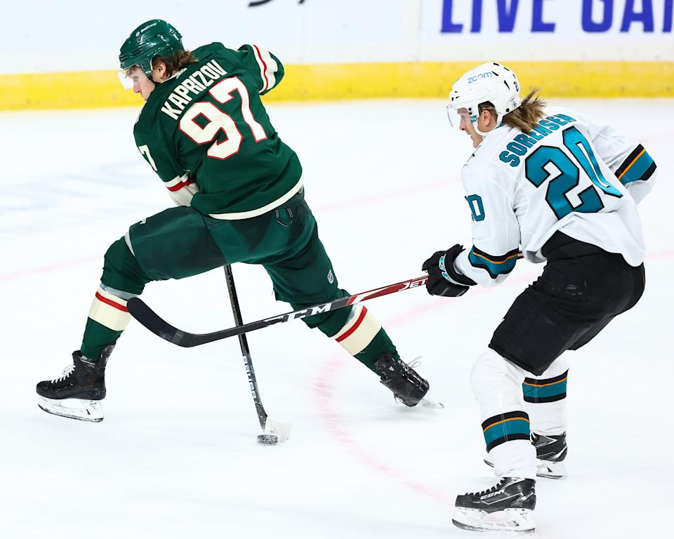 ST PAUL, MN - JANUARY 22: Kirill Kaprizov #97 of the Minnesota Wild attempts to pass the puck as Marcus Sorensen #20 of the San Jose Sharks defends him during the third period at Xcel Energy Center on January 22, 2021 in St Paul, Minnesota. (Photo by Harrison Barden/Getty Images)